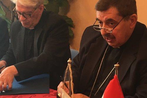 Kuvassa kirkkoherra Ilkka Järvinen ja piispa Branco Beric allekirjoittavat ystävyysseurakuntasopimuksen.